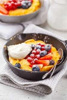 Dutch baby pancake with berries and cream in a cast-iron pan.