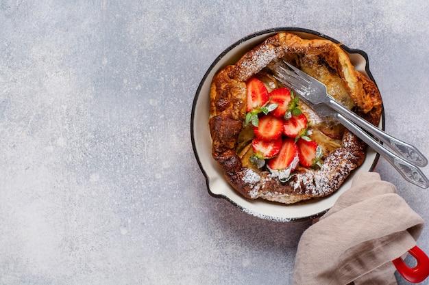 新鮮なイチゴのベリーと白いキッチンの背景に赤い鍋に粉砂糖を振りかけたダッチベイビーパンケーキ。上面図。