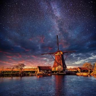 Голландская мельница ночью. звездное небо. голландия нидерланды.