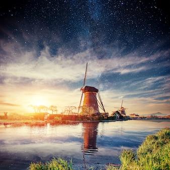 Голландская мельница ночью. звездное небо. голландия.