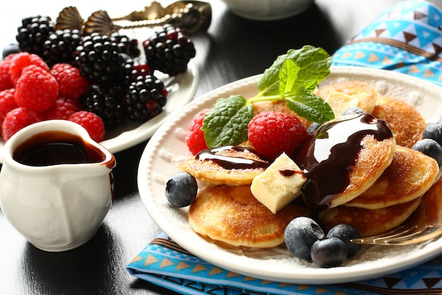 Dutch mini pancakes called poffertjes with berries and chocolate sauce