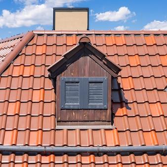 Голландская красная крыша с мансардным окном и закрытыми окнами. экстремальный крупный план.