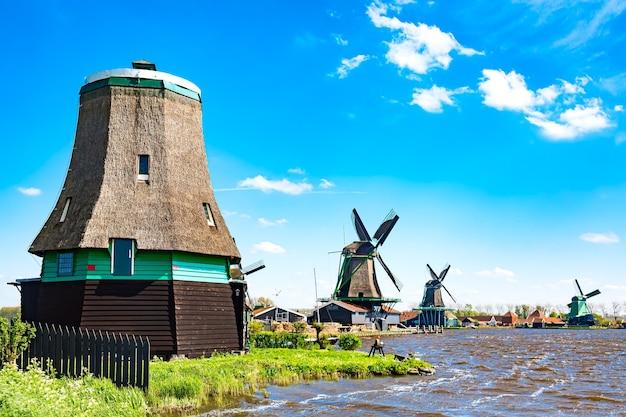 네덜란드의 전형적인 풍경입니다. 네덜란드 잔세스칸스(zaanse schans) 마을의 푸른 흐린 하늘을 배경으로 전통적인 옛 네덜란드 풍차. 유명한 관광지.