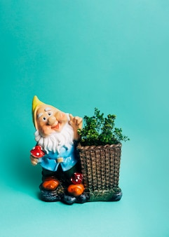 Dwarf figurine with show plant in the basket against colored backdrop
