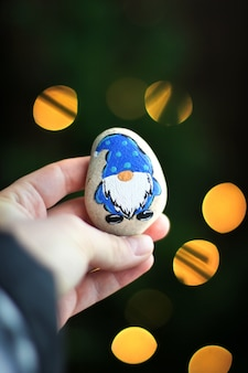 Карлик на камне. каменная игрушка в руке на фоне рождества. огни на заднем плане