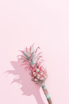 Карликовый орнаментальный мини-розовый цветок ананаса на розовом бумажном фоне с темными тенями. один тропический цветок на стебель