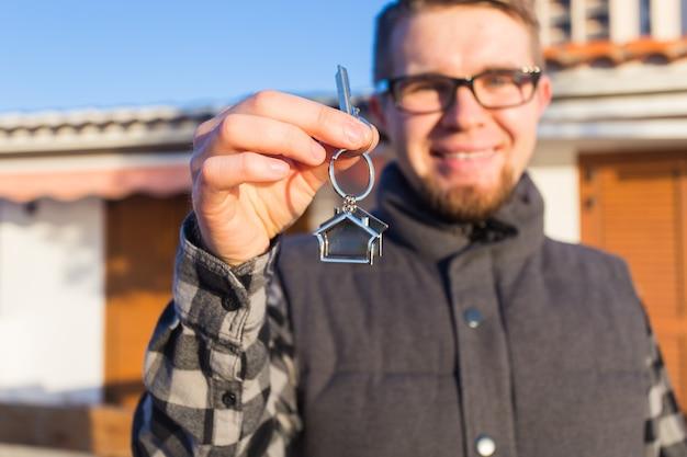 Жилище, покупка дома, недвижимость и концепция владения - красивый мужчина показывает свой ключ от нового дома
