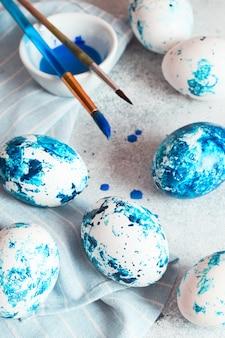 Окрашенные пасхальные яйца. синие крапчатые пасхальные яйца с краской и кистями.