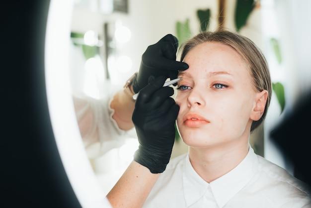 Окрашивание и формирование бровей. девушка в салоне красоты. выщипывание бровей пинцетом