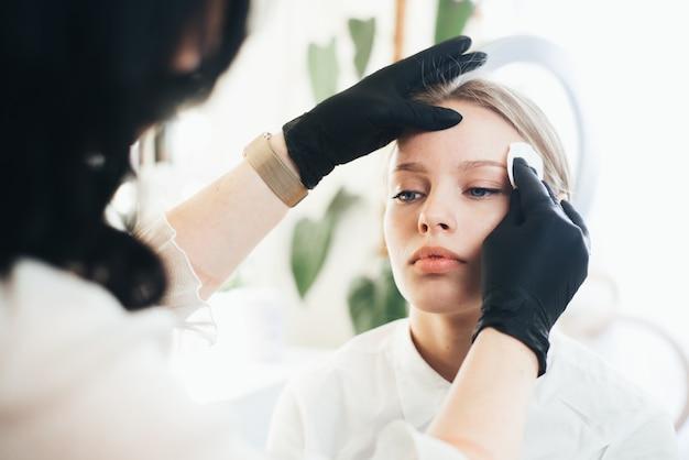 Окрашивание и формирование бровей. девушка в салоне красоты.
