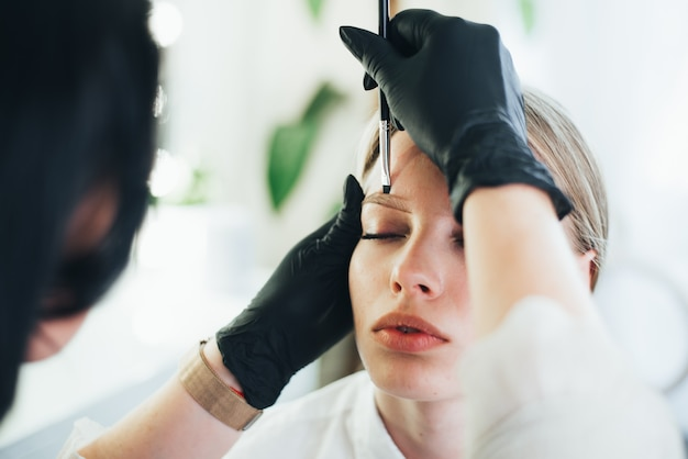 Dyeing and shaping of eyebrows. girl in a beauty salon.