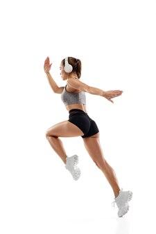 동적. 백인 전문 여성 운동선수, 흰색 스튜디오 배경에 격리된 주자 훈련. 근육질의 낚시를 좋아하는 여성. 행동, 운동, 젊음, 건강한 생활 방식의 개념. 광고에 대 한 copyspace입니다.