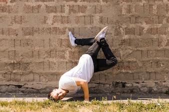 Dynamic modern style performer posing against wall