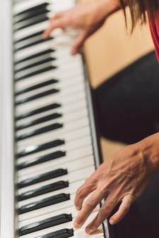 전자 피아노를 연주하는 여성의 손의 역동적인 수직 사진