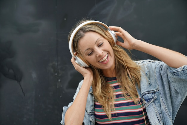 Dynamic young student listening to music with headphones