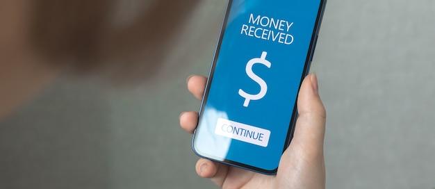 전자 뱅킹 및 전자 상거래 개념입니다. 온라인 뱅킹 응용 프로그램과 함께 휴대 전화를 사용하는 여성, 온라인 배경 사진 배너로 돈 받기