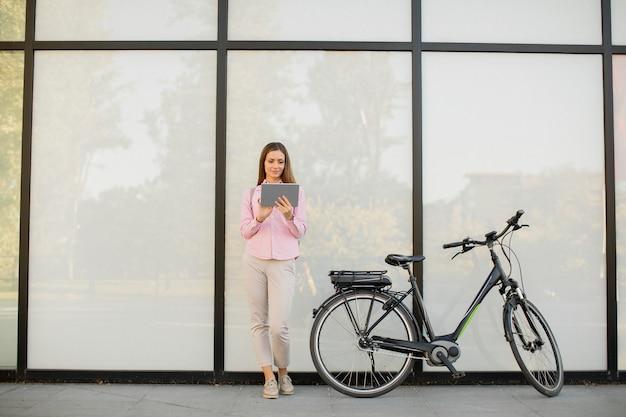 Молодая женщина с планшетом и e-bike на открытом воздухе