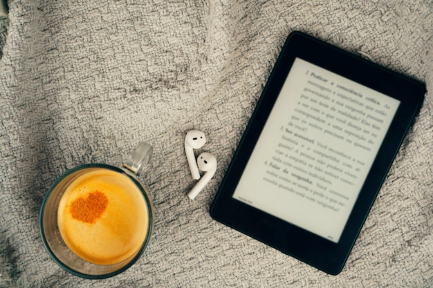 E-book reader, a cup of coffee and a earphone.