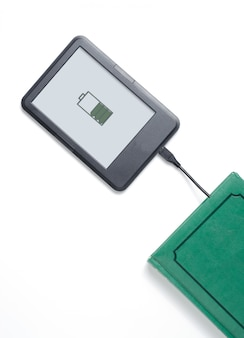 E-book reader and green book connected with cable.