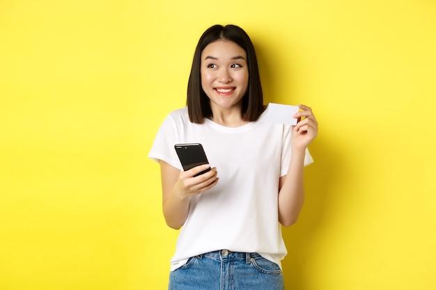 전자 상거래 및 온라인 쇼핑 개념. 쾌활 한 아시아 여자 인터넷에서 지불, 스마트 폰 및 플라스틱 신용 카드를 들고 웃 고 찾고 왼쪽, 노란색 배경.