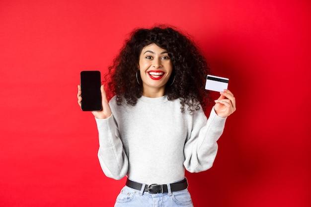 전자 상거래 및 온라인 쇼핑 개념입니다. 빨간 배경에 서서 플라스틱 신용카드와 빈 스마트폰 화면을 보여주며 웃고 있는 쾌활한 여성.