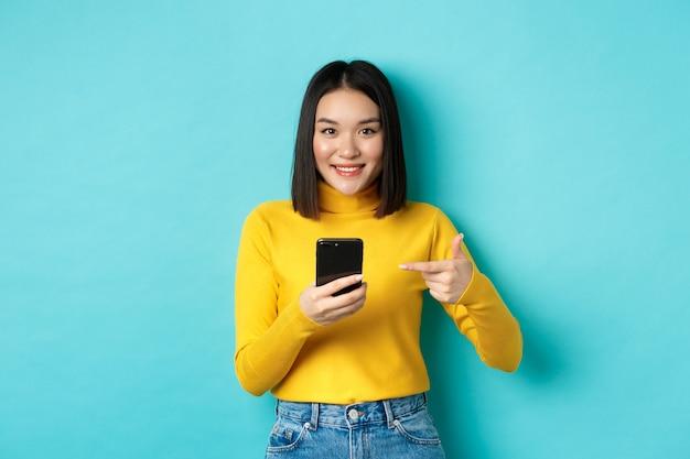 전자 상거래 및 온라인 쇼핑 개념. 블루 위에 서 카메라에 웃 고 스마트 폰에서 가리키는 노란색 스웨터에 귀여운 아시아 여자.