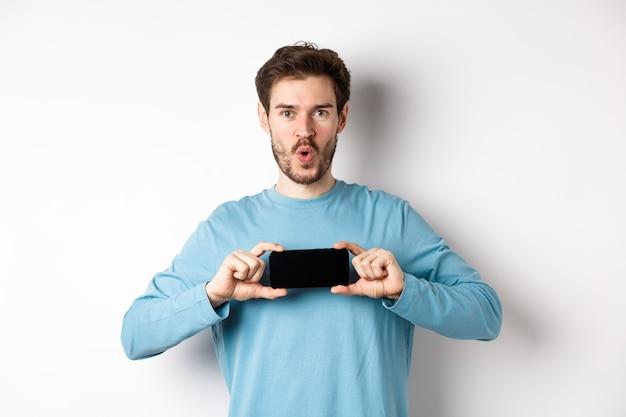 전자 상거래 및 쇼핑 개념. 와우를 말하고 흰색 배경 위에 서있는 수평으로 빈 휴대 전화 화면을 보여주는 감동적인 남자의 이미지.