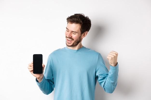 전자 상거래 및 쇼핑 개념. 행운의 남자 온라인 승리, 빈 스마트 폰 화면을 표시하고 승리, 주먹 펌프로 예라고 말하고, 흰색 배경 위에 서 있습니다.