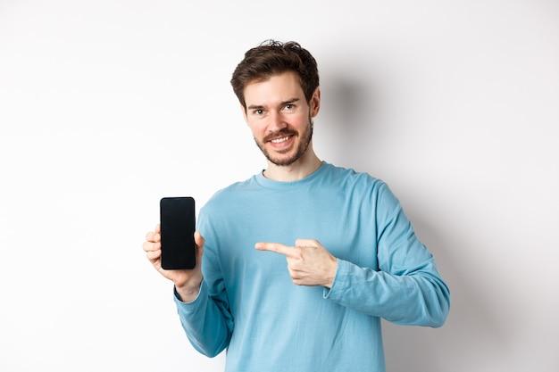 전자 상거래 및 쇼핑 개념. 빈 스마트 폰 화면에서 백인 남자 가리키는 손가락, 온라인 제안, 흰색 배경을 보여주는 미소.