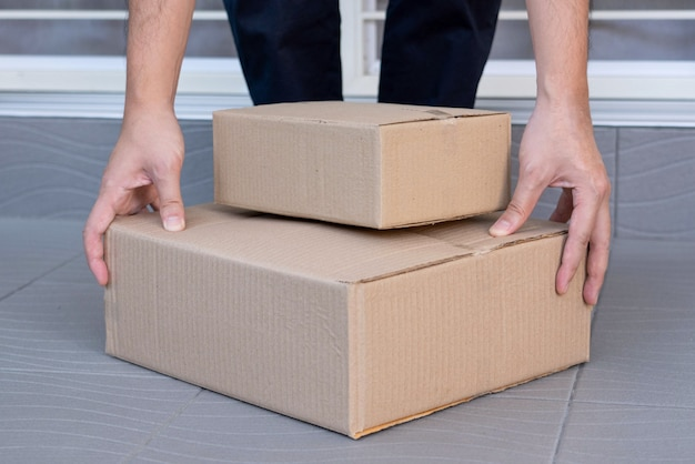 E-commerce concept a man leaving home and lifting the boxes for sending them to his customers via tracking express.