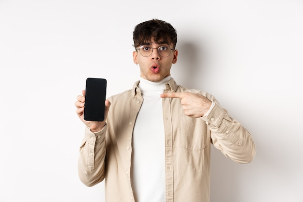 Eコマースの概念。携帯電話の画面を指して、オンラインで広告を表示し、白い背景の上に立っている若い男の肖像画