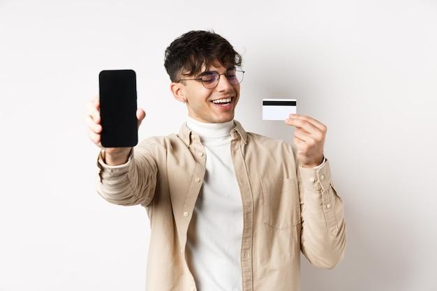 Eコマース。プラスチックのクレジットカードに満足しているように見える幸せな若い男は、白い壁に立って、自慢するスマートフォンの画面を示しています。