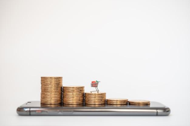 전자 상거래, 돈 및 금융 개념. 미니어처 쇼핑 카트의 근접 촬영 / 모바일 스마트 폰에 동전 더미에 트롤리