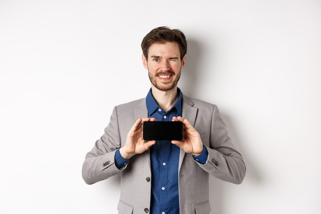 E-commerce and online shopping concept. cheeky male model in suit winking and showing empty smartphone screen, smiling happy at camera, white background.