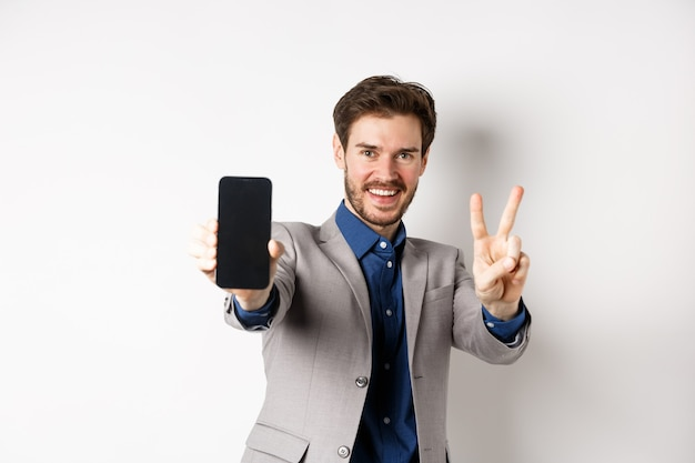 E-commerce and online shopping concept. cheerful man in business suit showing v-sign and empty mobile phone screen, demonstrate smartphone app, white background.