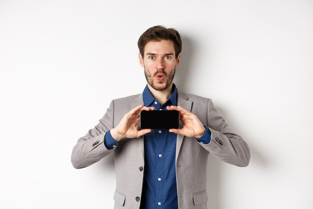 E-commerce and online shopping concept. excited young man in business suit show empty smartphone screen and say wow amazed, white background.