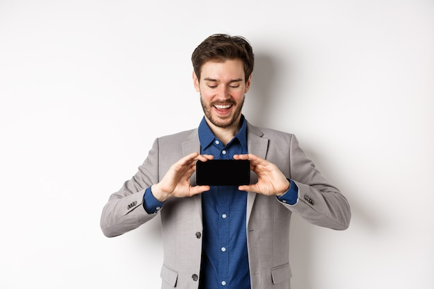 E-commerce and online shopping concept. happy young man in suit laughing, showing empty smartphone screen horizontally, wite background.