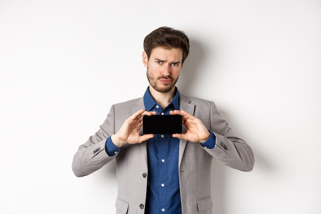 E-commerce and online shopping concept. hesitant frowning man showing empty smartphone screen, standing on white background.
