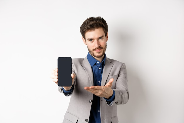 E-commerce and online shopping concept. man demonstrated empty smartphone screen to you, showing phone display to introduce something, standing on white background.