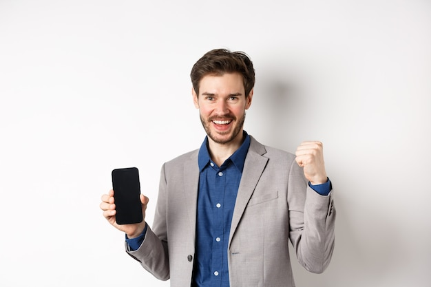 E-commerce and online shopping concept. man making money in internet, showing smartphone screen and winner gesture, smiling satisfied, standing on white background.