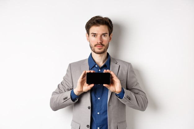 E-commerce and online shopping concept. serious young man in suit showing empty smartphone screen horizontal, standing on white background.