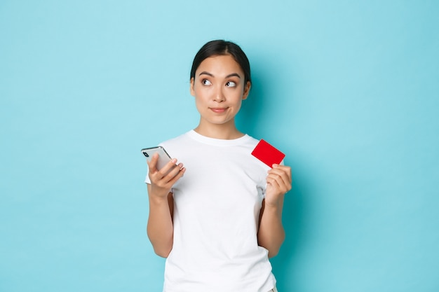Eコマース、ショッピング、ライフスタイルのコンセプト。白いtシャツを着た優柔不断な思いやりのあるアジアの女の子、クレジットカードとスマートフォンを持って考えながら目をそらし、オンライン注文をします。