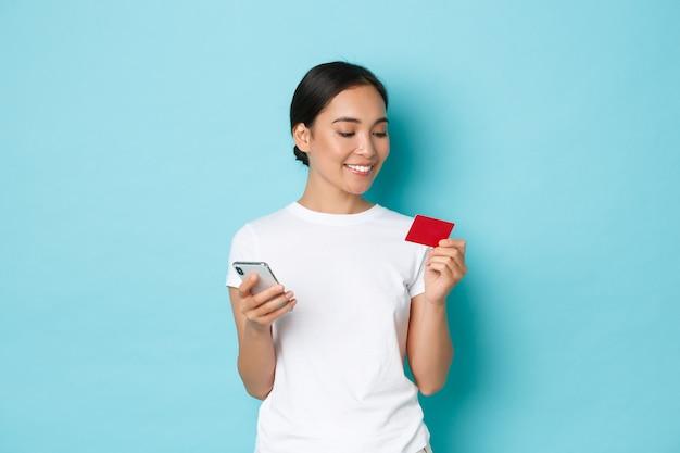 Eコマース、ショッピング、ライフスタイルのコンセプト。魅力的なアジアの女の子がオンラインで注文する笑顔、携帯電話アプリに数字を入力しながらクレジットカードを見て、水色の壁に立っています。