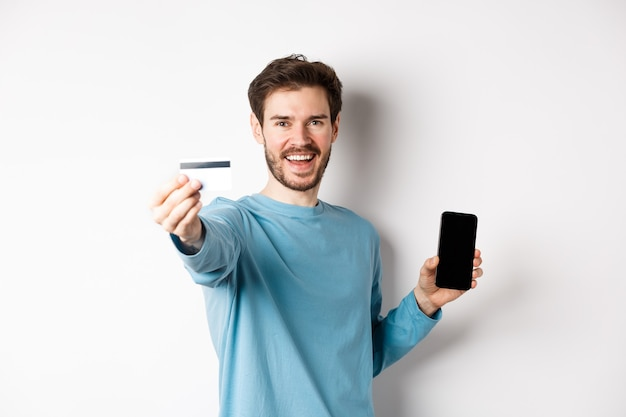 E-commerce and shopping concept. happy man showing plastic credit card and screen of smartphone, recommending banking app, standing on white background.