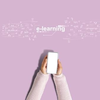 Eラーニングの概念。手は、ピンクの背景にスマートフォンを持っています。