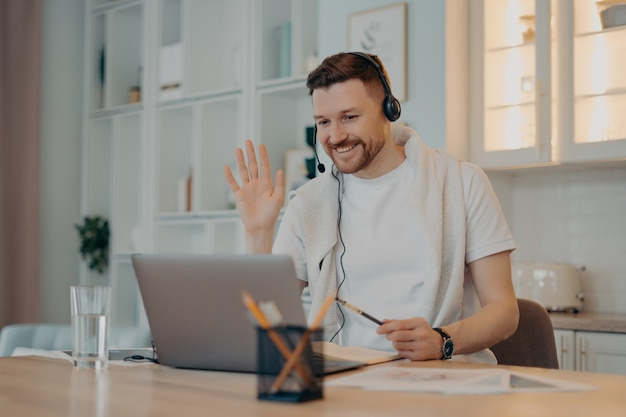 E learning concept. happy bearded man student has video conference studies online waves palm in laptop display greets teacher works distantly uses headset makes notes in diary poses over home interior