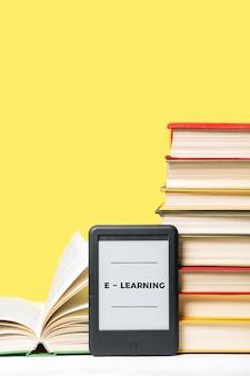 Электронное обучение. читатель электронных книг и стопка книг на желтом