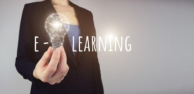 Eラーニングオンライン学習遠隔教育の概念。ハンドホールドデジタルライトバルブ。電球で明るいアイデアをネットワーク化します。