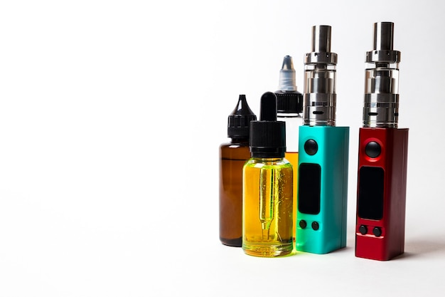 E- liquid in the bottles and vape on the white background