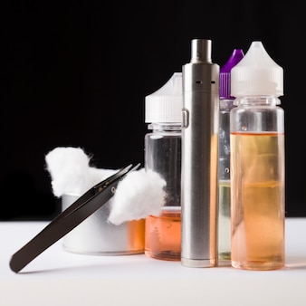 E-liquids, cotton, tweezers and electronic cigarrette for vaping